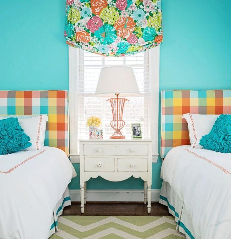 chambre enfants avec murs turquoise et têtes de lit à carrés en couleurs