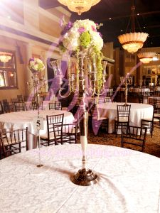#Centerpiece contains #white and #green #hydrangeas, #purple #roses and green #hanging fillers. Set up on tall #candelabra within the middle of every tables. These centerpiece design not only #beautiful but also fill up well in this large size #wedding #reception #hall.