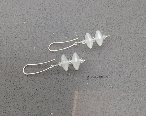 """Inspired by mid-century modern and art deco light pendants but with a modern twist, these fun, swingy earrings are made using handmade lampwork glass saucers from SueBeads, Swarovski crystals and extra-long sterling silver ear wires earrings  Earrings – 2"""" (51mm) long by 5/8"""" (15mm)"""