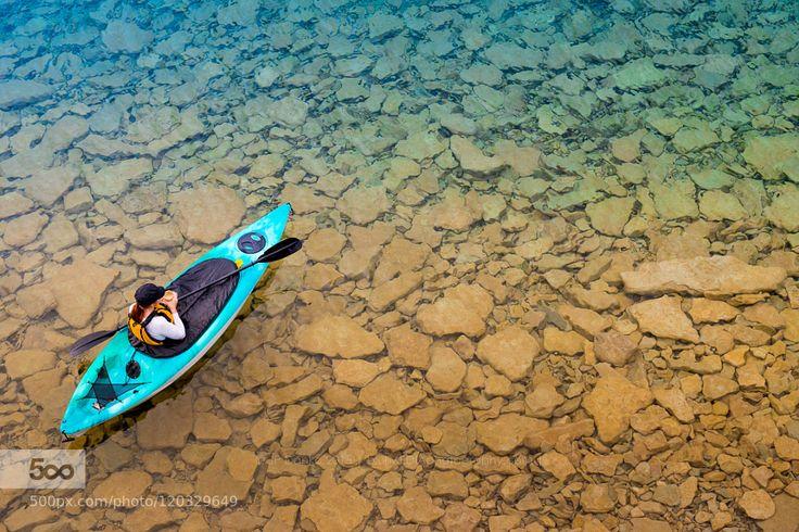 Woman in Sea Kayak Paddling on Georgian Bay by blurMEDIA