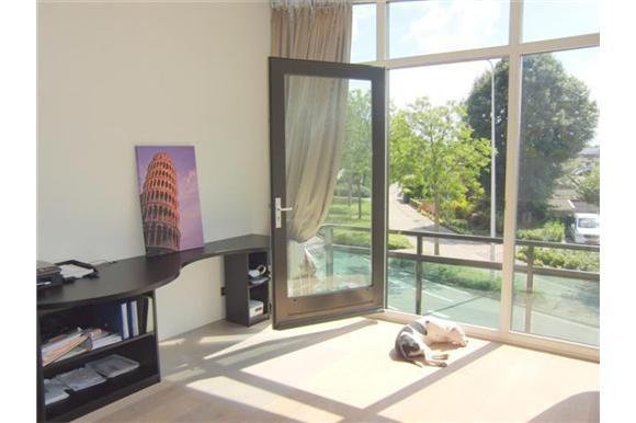 Slaap/werkkamer 1 vind je aan de voorzijde met vast bureaublad en deur naar een zonnig balkon met uitzicht over de schitterende panden gelegen aan de Oudshoornseweg.