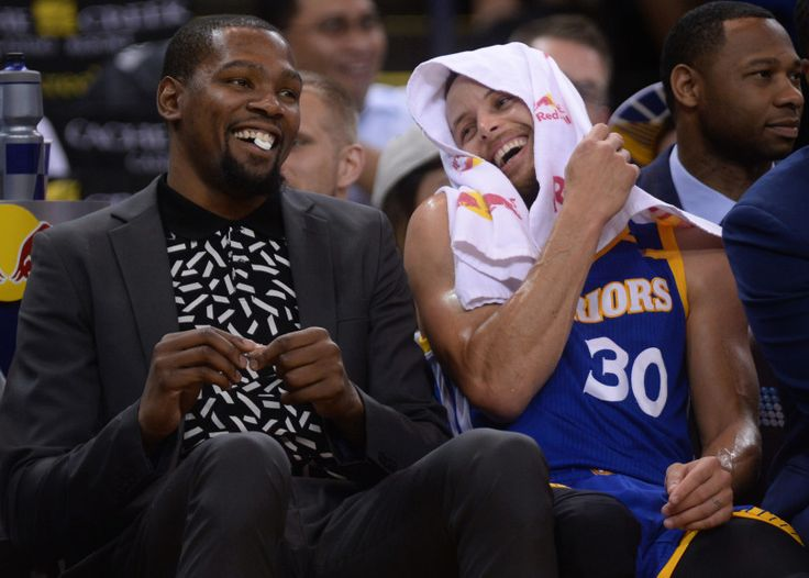Golden State Warriors' Kevin Durant (35) and Stephen Curry (30) enjoy a light moment together on the bench after a photograph of Draymond Green flashes on the big screen and team members attached a caption to it late in their game against the Washington Wizards at Oracle Arena in Oakland, Calif., on Sunday, April 2, 2017. (Susan Tripp Pollard/Bay Area News Group)