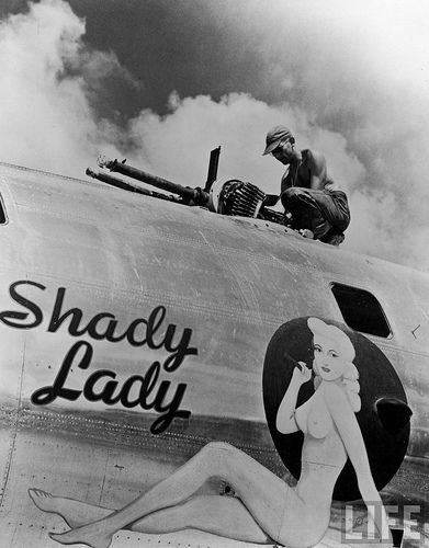 """B-29 """"Shady Lady""""  Ground crew member adjusting machine guns on a B-29 Superfortress named """"Shady Lady"""" from the 497th Bomb Group.  Saipan,Marianas Islands;1945."""