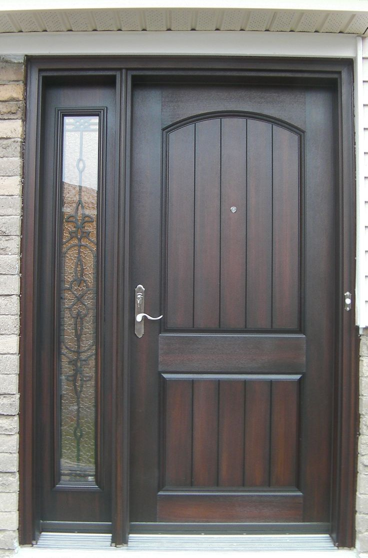cambered two panel plank rustic fiberglass door with wrought iron sidelite in a light walnut stain