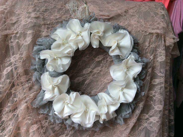 Handmade grey lace wreath with cream rosette flowers.
