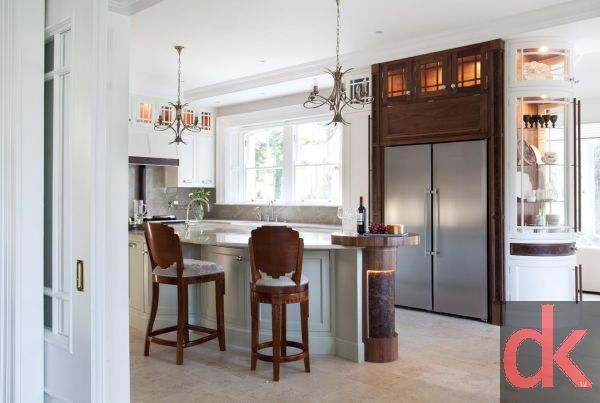Luxury hand painted kitchen cabinetry with walnut kitchen cabinetry doors with burr walnut accents.  Curved glass kitchen doors with custom inlay.  Exotic stone worktops along with custom made dining table and chairs