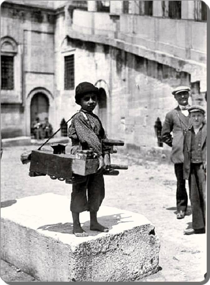 A young AYAKKABI BOYACISI (shoeshiner). Near the Yeni Camii, Eminönü, Istanbul. 1930s.