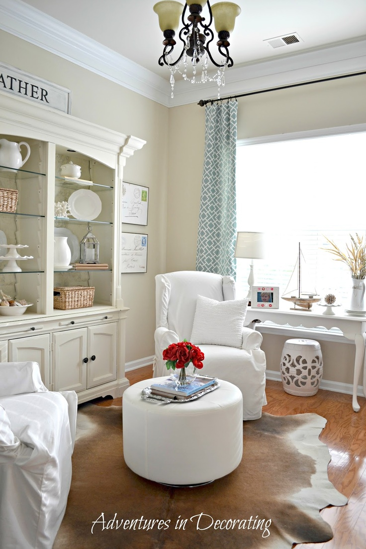 Cozy Sitting Room: Painted Large Shelving/cabinet, Printed Curtains, Ceramic  Stool, Sofa Table Under Window.