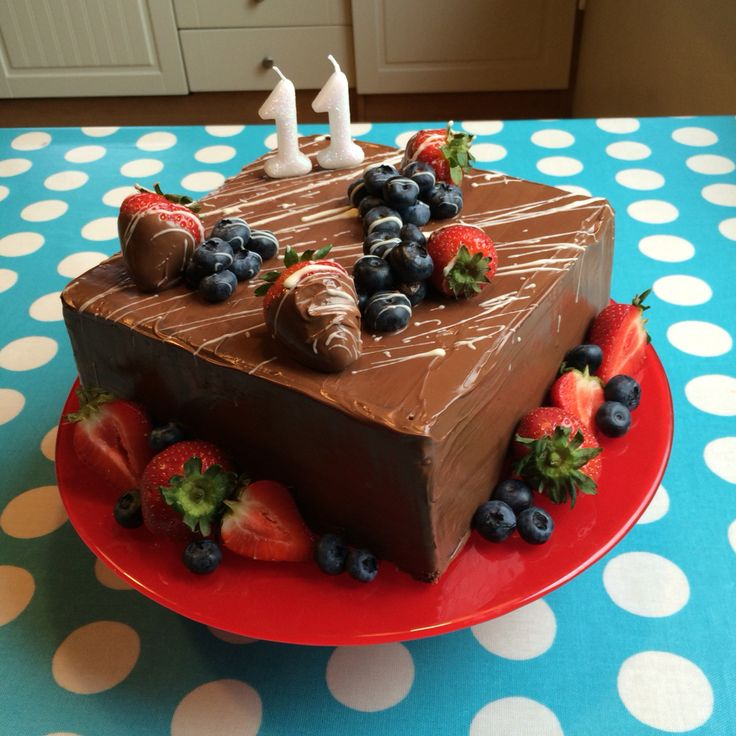 Chocolate biscuit cake covered in chocolate, with strawberries and blueberries.