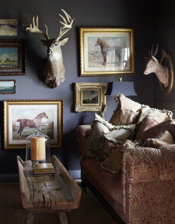 In this study, a vintage hay trough was used for a coffee table in front of the sofa piled high with down filled cushions made with antique tapestries. The art wall features equine works as well as the homeowners prize buck and antique trophy horns.