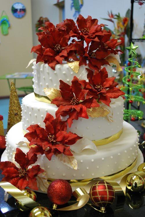 Hermoso centro de mesa, UN PASTEL DE NAVIDAD con guirnaldas de flores rojas.