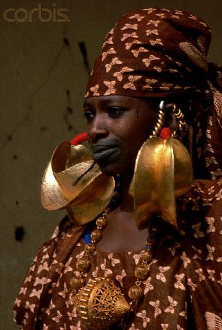 Africa | A Fulani/Peul woman wears large gold earrings and necklace. She also has her lips tattooed in the traditional style. Mali | © Charles  Josette Lenars