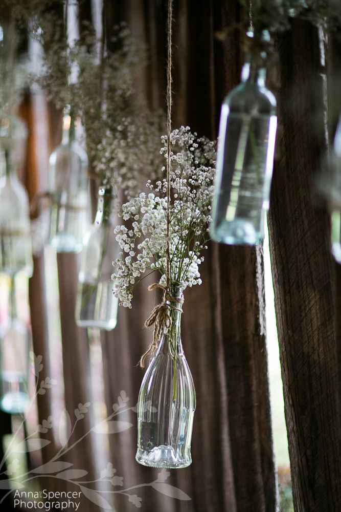 Anna and Spencer Photography, Atlanta Documentary Wedding Photographers. Simple baby's breath Flowers in Glass Bottles at a Barn Wedding Reception.