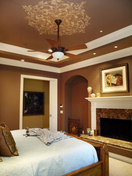Rich color above is the perfect choice for this bedroom, with its tray ceiling and double row of wide white crown molding. All that warm brown makes the architecture pop. The decorative detail around the ceiling fan is an extra bonus.
