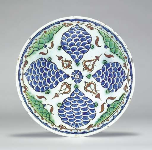 A RIMLESS IZNIK POTTERY DISH  OTTOMAN TURKEY, CIRCA 1630  With rounded sides, the white interior decorated in blue, green, black and red with four cusped ogival blue fish-scale cartouches radiating around a central small blue rosette with red arabesque panels and similar green fish-scale half-cartouches between, the narrow blue and white arcaded border with red dots, the exterior with alternating blue and green motifs,   10 1/8in. (25.7cm.) diam.