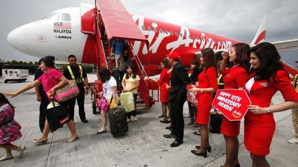 AirAsia staff greet passengers arriving from Kota Kinabalu to the Low Cost Carrier Terminal in Sepang outside Kuala Lumpur December 8, 2011, during its 10th year anniversary celebrations.  AirAsia started from two aircraft and three destinations in December 2001 to over 80 destinations in 24 countries and 107 aircraft groupwide, AirAsia press release stated.  REUTERS/Bazuki Muhammad (MALAYSIA - Tags: TRANSPORT) - GM1E7C816MO01 #lowcostflights