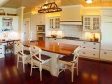 Custom hood, glass wall cabinets, pot rack on island