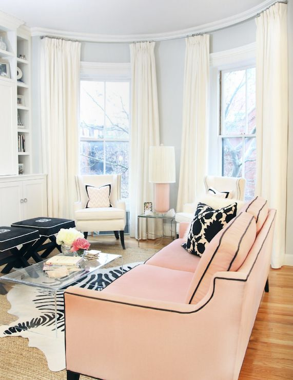 Erin Gates Design    Gorgeous chic city living room design with gray walls, pink sofa with black piping and white & black Thomas Paul flock pillows, zebra cowhide rug layered over jute rug, CB2 peekaboo acrylic cocktail table, black monogrammed x-benches with white piping, pink lamp, white wingback chairs with pink zigzag chevron pillows