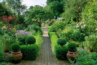 Private garden. Sussex. Brick path lined with boxwood hedges. Mixed planting of roses and perennials. View through to iron gates.  Copyright  John Glover