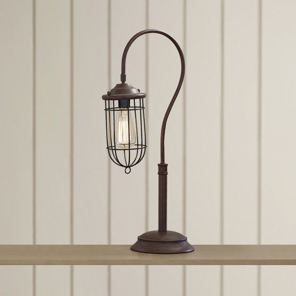 Evoking the elegance of an antique lantern, this charming table lamp features a cage-inspired shade and reddish bronze finish. Set it beside a stack of vintaged art books for a timeless end table vignette, or add it to the master suite to cast a warm glow on your bedside table.