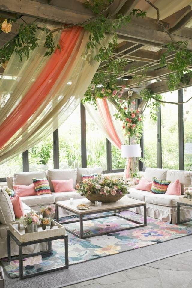 véranda vitrée et aménagée avec canapés blancs, tapis et rideaux
