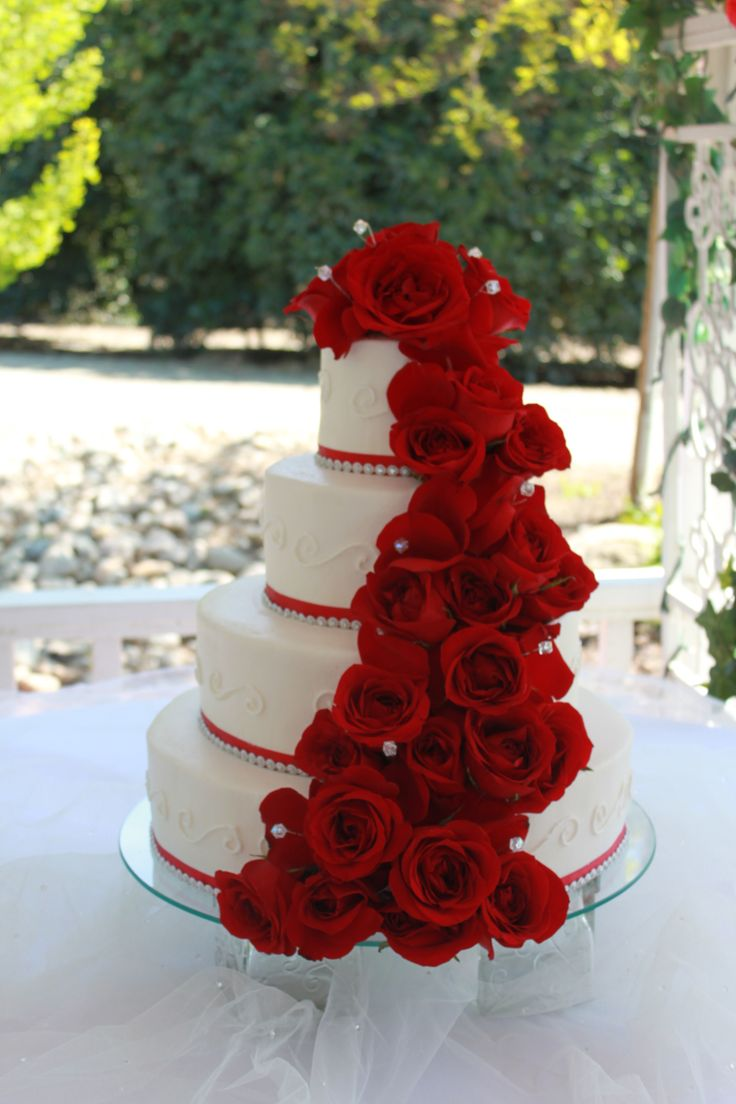 Love the way the flowers drape from the top and around the cake.  The color contrast is nice, but could also look nice to mix and match some ivory flowers and the main cake to be ivory.  Rhinestones preferred, but pearls are also nice. With or without a ribbon would look great.