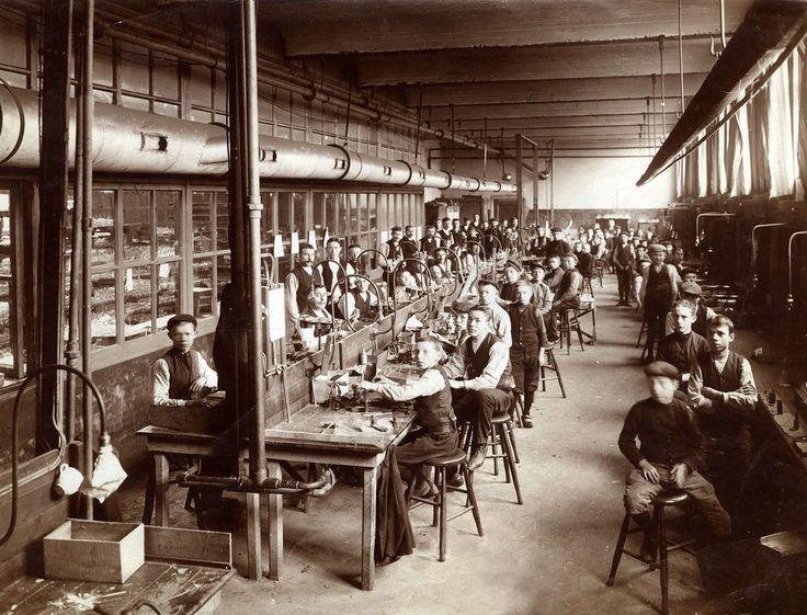 Lampenfabricage in Nederland. Een kijkje in de glasblazerij van Popes Metaaldraad-lampenfabriek. Jongens en jongemannen (kinderarbeid)gezeten op krukken aan met elektrische verlichting voorziene werktafels verwerken glazen elektrische peertjes. Venlo, 1909.