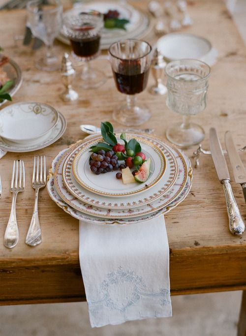 Interesting balance of styles between the antique and romantic look of the tableware against the raw natural wood of the kitchen table...