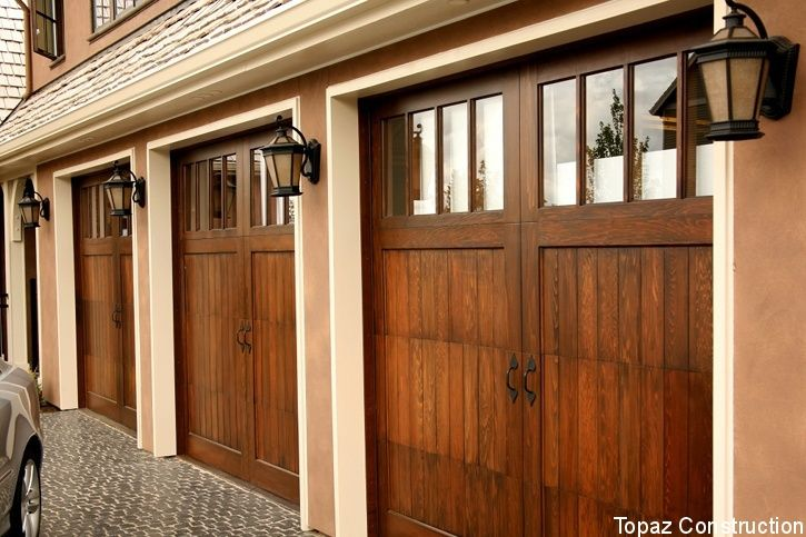 Wood garage doors are always a good choice. This three-car garage has wall sconces beside each of the multi-light windows. On average it costs homeowners $964 to install a garage door.