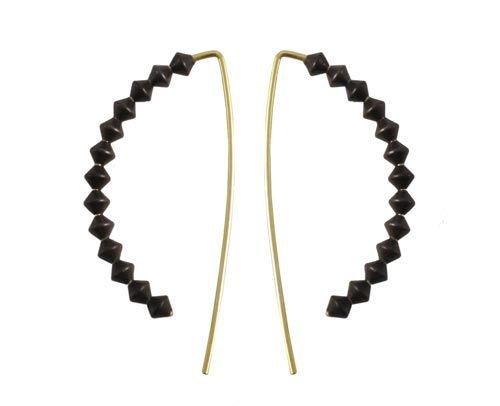 Øreringe med bicones Til denne ørekrog skal der bruges følgende materialer:  1 par ørekroge, forgyldt sterlingsølv 26 stk. bicone 3mm, sort messing + lim  Der påføres en smule lim øverst på ørekrogen hvor den først bicone skal sidde. Den første bicone føres på og limes fast. Fortsæt med at føre bicones på ørekrogen og under den sidste bicone påføres også lidt lim på ørekrogen så den sidder ordentlig fast. Der kan evt. også påføres en smule lim midt i rækken af bicones.