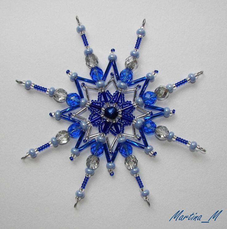 Vánoční hvězda 31 modrostříbrná Vánoční hvězdička střední velikosti z plastových a skleněných korálků a perliček v odstínech modré a stříbrné barvě. Průměr 11.5 cm, díky koncovým očkům lze zavěsit na háček. Pouze 1 ks - originál.