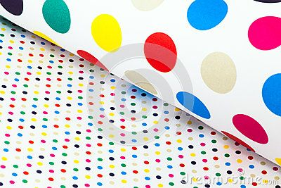 Roll and flat white sheets of wrapping paper with colorful spots or dots.