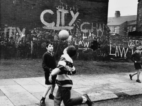 Boys Play Football in the Street - Moss Side, Manchester Photographic Print by Shirley Baker at Art.co.uk