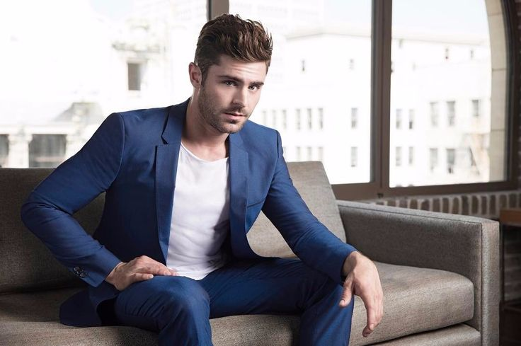 Zac Efron sitting on a sofa with his hand on his thigh, another hand is resting on his knee.