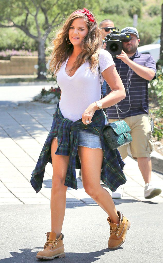 Khloé Kardashian Odom cools off on a hot summer day in cutoffs, white V-neck and Timberland boots. #style
