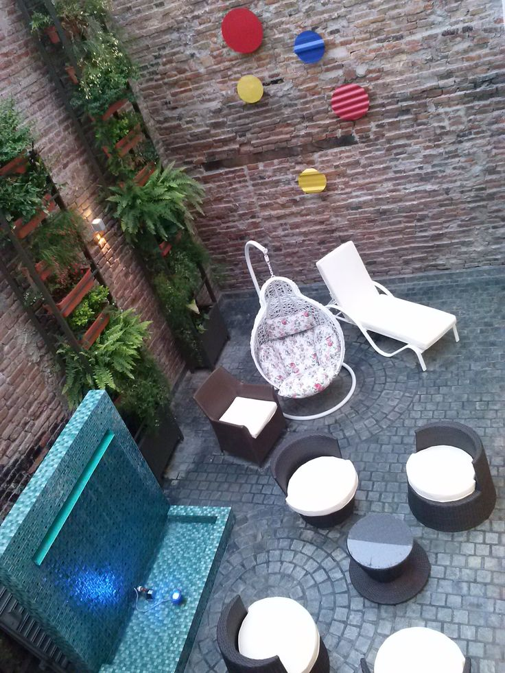 Patio, fuente, detalles en chapa pintada, piso en adoquin de laja. Estudio Juarez Lico