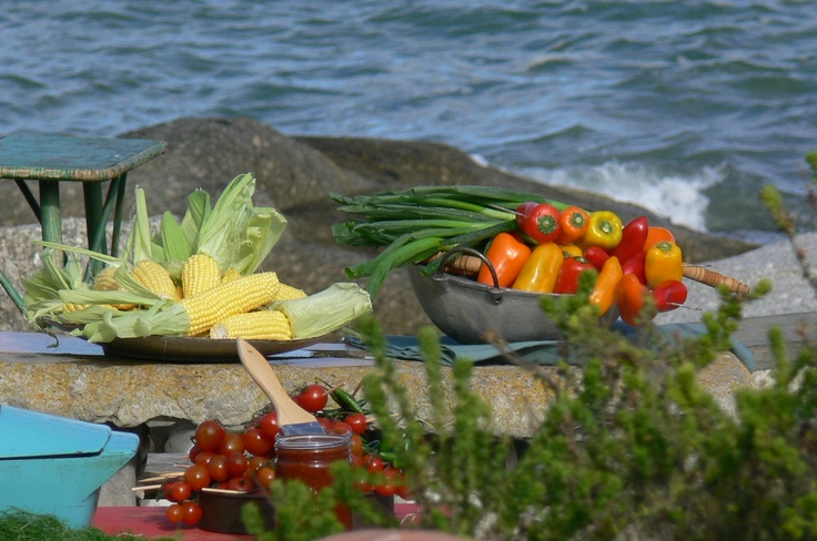 Corn on the cob on the braai plus array of peppers with backdrop of the sea