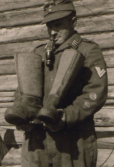fallschirmjager:  Luftwaffe Flak Obergefreiter examining his Ost winter boots Russia, 1942. Seriously that jager-pipe is suave.   Also notice his drivers proficiency badge & his Luftwaffe drivers badge.