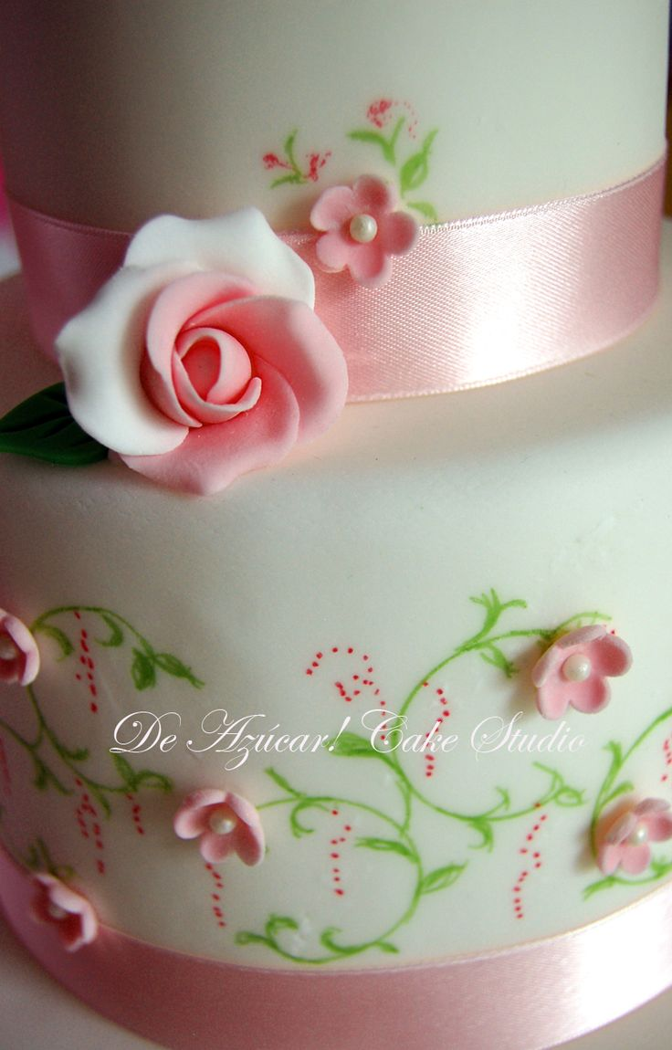 A Small Wedding Cake With Painted Vines Leaves And