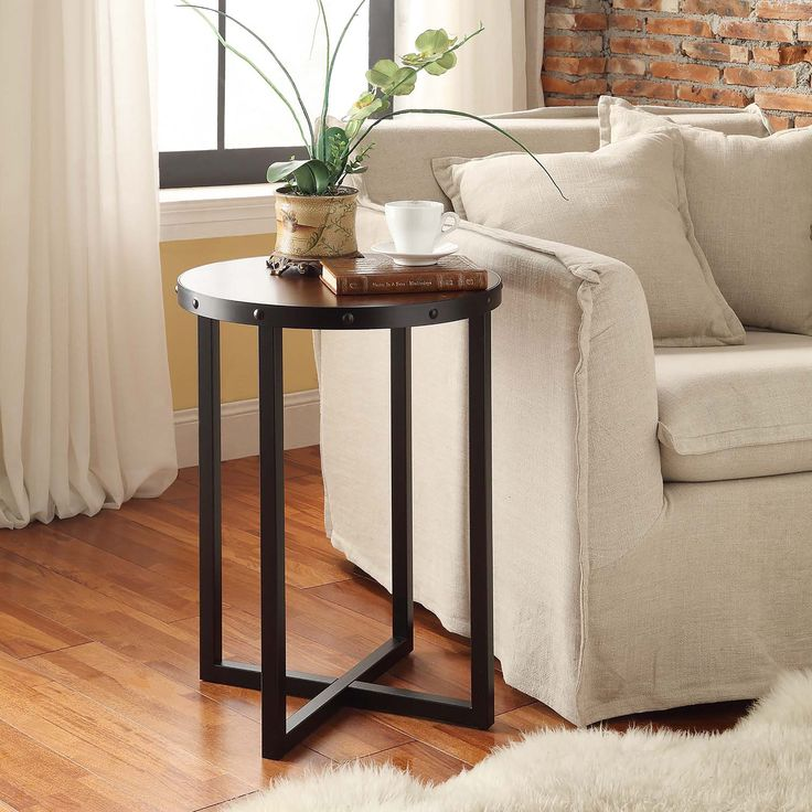This tall accent table has metal leg construction and a chestnut wooden top. Its round surface is supported with a squared four-way base that offers excellent support.