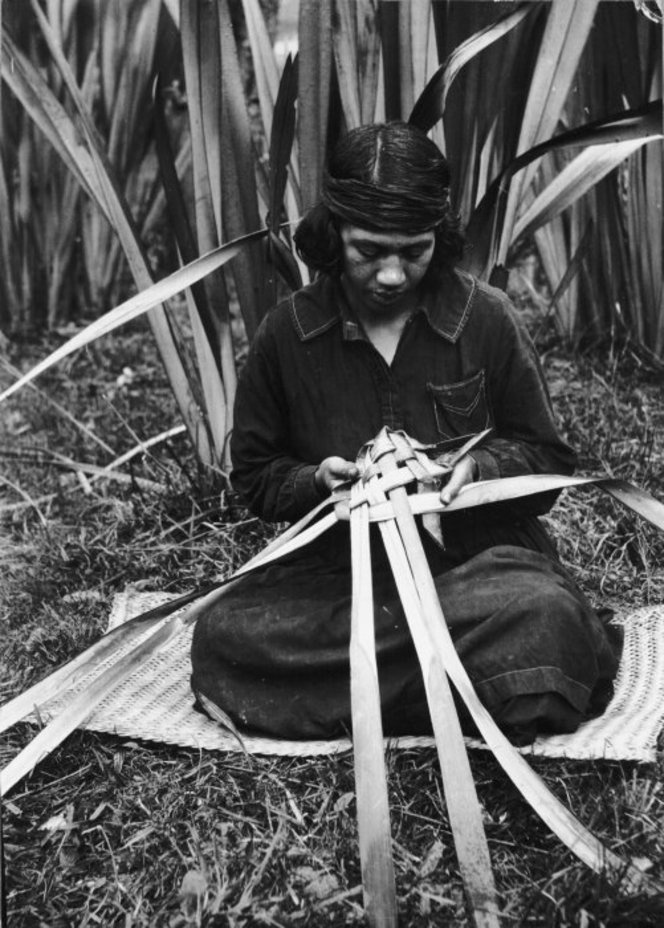Woman weaving a food basket (rourou or kono) from flax leaves, at Koroniti