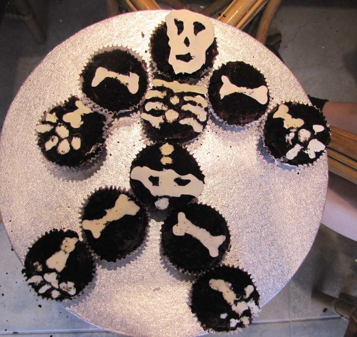 Spooky deconstructed skeleton Halloween cupcakes.  Pipe/form white melted chocolate as skeleton bones on wax paper then apply to chocolate cookie crumb-covered cupcakes to make it look like soil! I made these for Halloween 2010 :)