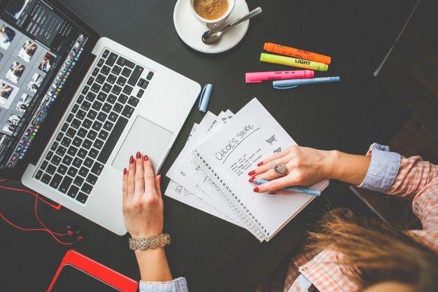 Mulher que trabalha em sua mesa de escritório Foto gratuita