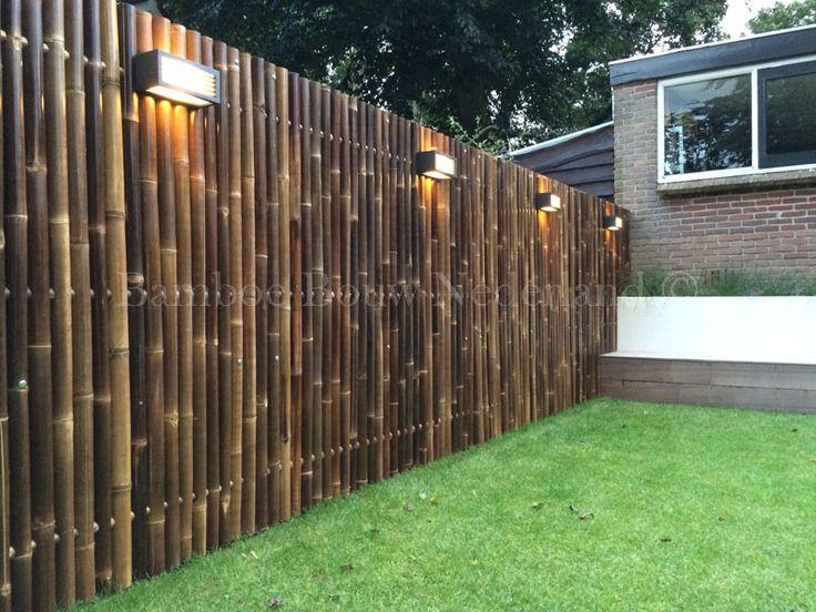 De strakke robuuste Giant bamboeschermen, gecombineerd met groen gras en prachtige verlichting