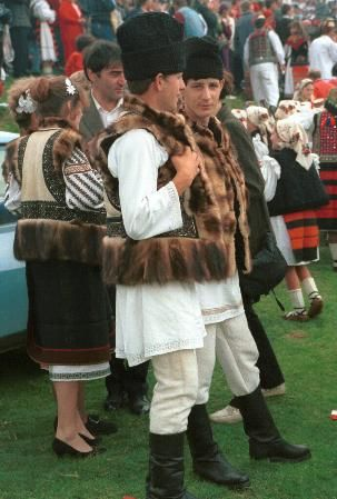 Romanian costume Câmpulung Moldovenesc - Suceava (Moldavia) Sheepskin jackets from Câmpulung Moldovenesc, Suceava, 1997 Sheepskin pieptar, edged with polecat fur and decorated with bands of embroidery in black and dark blue, purple and green, worn by both men and women. High Black căciulă (sheepskin shepherds hat)    Photo taken at Hora Prislop festival, August 1997
