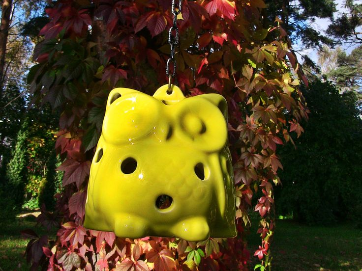 Ceramic yellow owl is hanged by a chain. Use it in your garden or terrace as an element of decor.