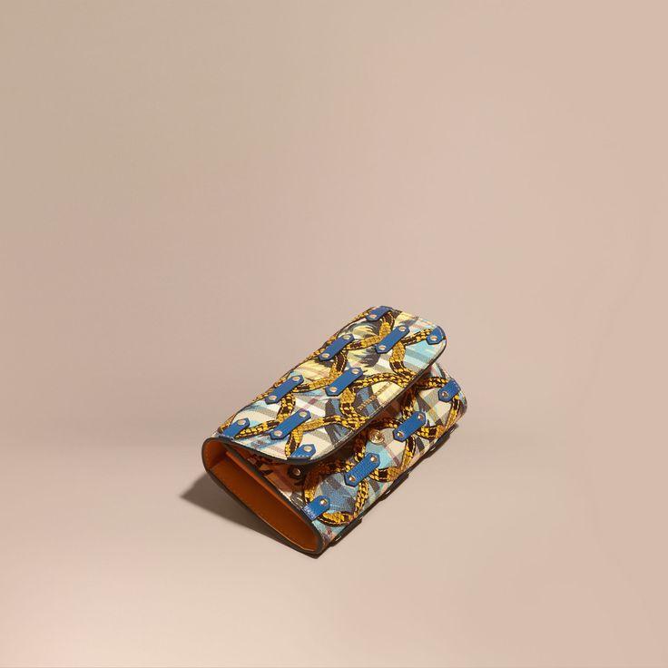 Portefeuille continental confectionné en Italie, arborant un motif Haymarket check rehaussé d'un imprimé à pivoines roses évoquant les tissus des défilés. Ce modèle est orné d'appliqués en peau de serpent et de cuir clouté pour un effet texturé resplendissant.