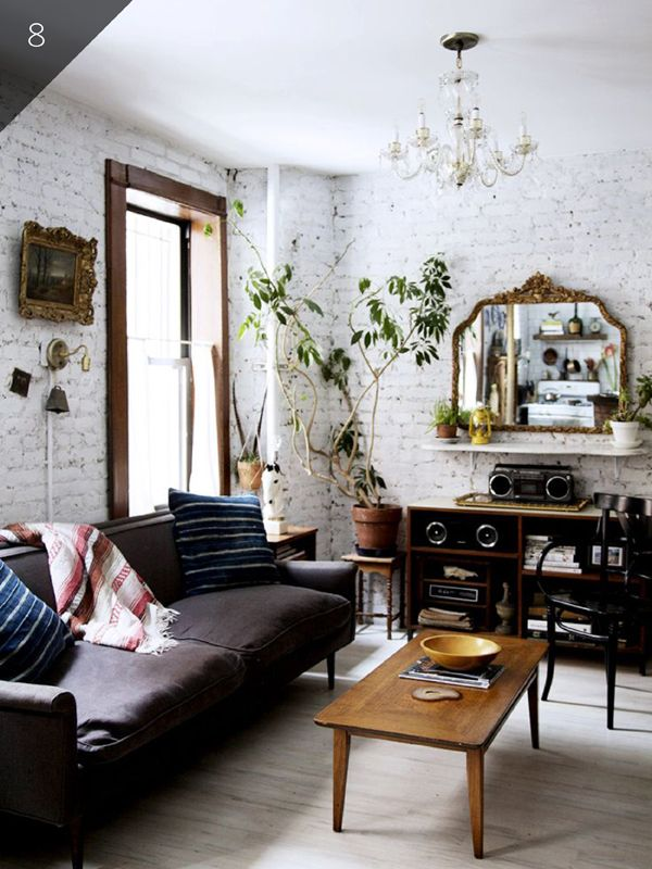 Loft living room with exposed brick, chandelier and gold mirror