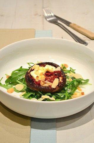 Gevulde portobello met geitenkaas, zongedroogde tomaatjes en geroosterde amandelen.