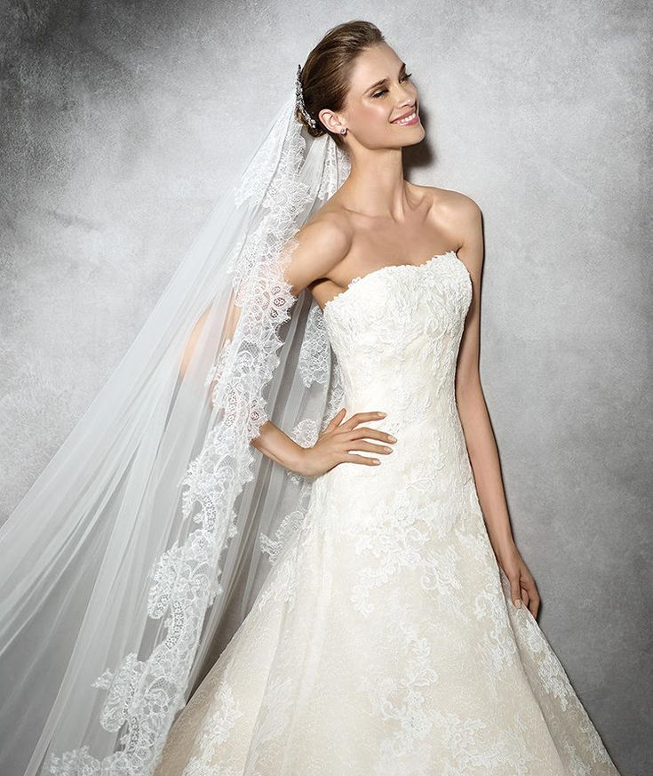 TAMIA- A-line lace dress with sweetheart neckline and beige lining. Bodice with sheer detachable overlay decorated with lace and thread embroidery. A-line lace skirt.
